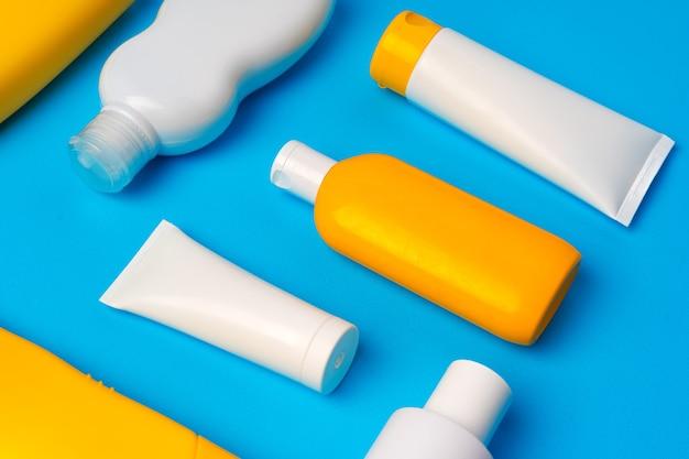 Bottiglie di crema solare su blu, piatto lay