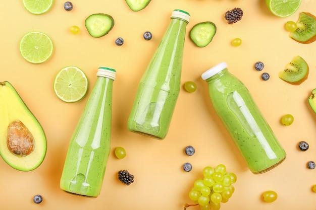 Bottiglie di gustoso frullato verde con ingredienti sulla superficie del colore