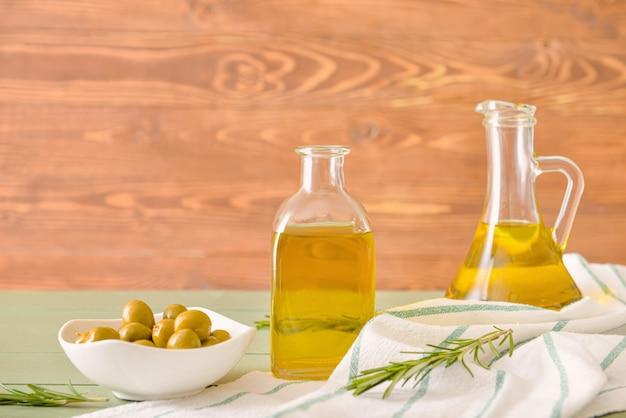 Bottiglie di gustoso olio d'oliva sulla tavola di legno