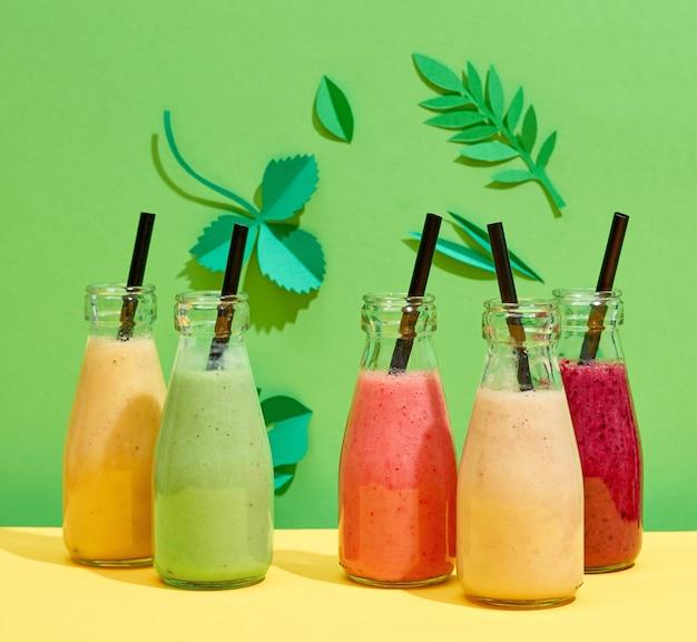 Bottiglie di vari frullati colorati di banane e bacche su sfondo di foglie di carta verde
