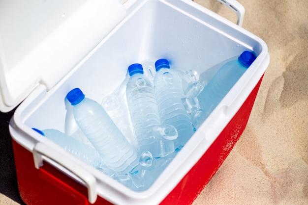 Bottiglie d'acqua nella ghiacciaia sulla spiaggia
