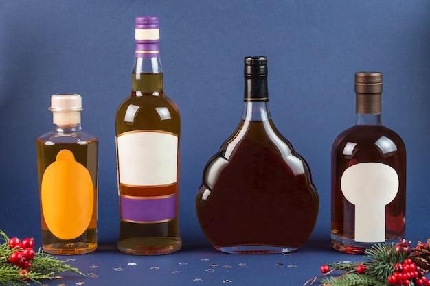 Bottiglie di whisky e brandy su un primo piano sfondo blu scuro. capodanno e natale.