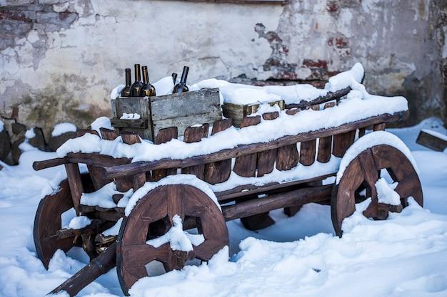 Bottiglie di vino in una scatola di legno su un carrello in inverno. foto di alta qualità
