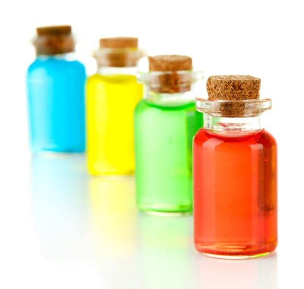 Bottiglie con liquidi colorati isolati su bianco