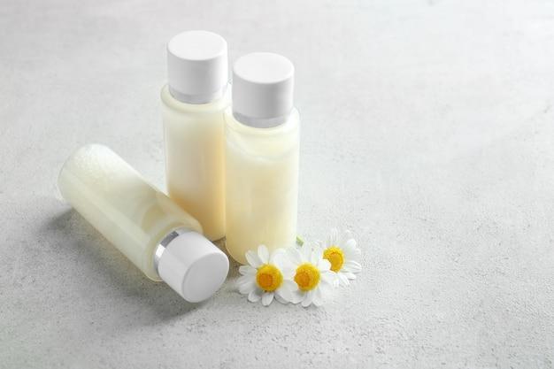 Bottiglie con crema e fiori di camomilla sul tavolo