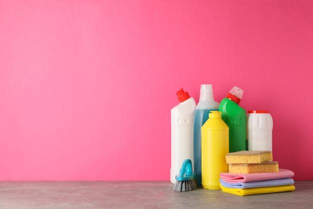 Bottiglie con detergente e prodotti per la pulizia sul rosa, spazio per il testo