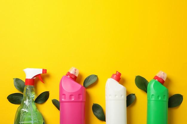 Bottiglie con detersivo e foglie su sfondo giallo, spazio per il testo