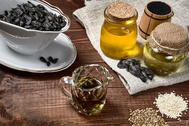 Bottiglie con diversi tipi di olio vegetale con semi di sesamo girasole e cumino nero