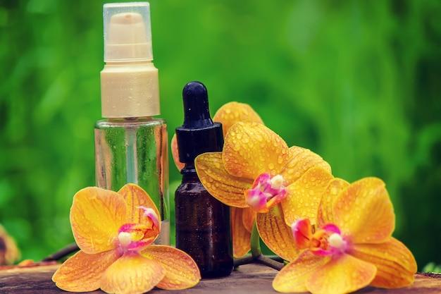 Bottiglie con oli essenziali e orchidea a minsk su una superficie in legno