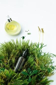 Flaconi con sieri cosmetici naturali per la cura del viso e del corpo con piante fresche. concetto di cosmetici biologici spa