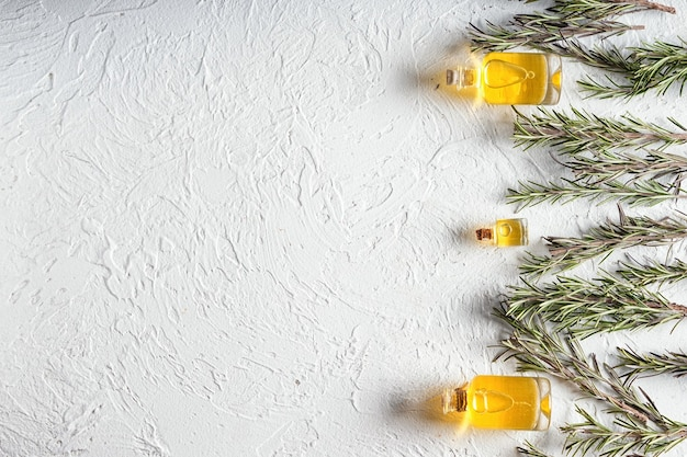 Bottiglie con olio di rosmarino su sfondo bianco
