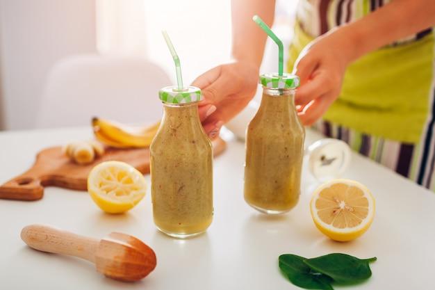 Bottiglie con spinaci e frullato di banana con ingredienti. la donna mette le bevande sul tavolo della cucina. dieta disintossicante sana