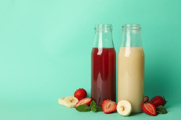 Bottiglie con succhi di fragola e banana su menta