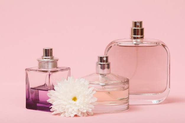 Bottiglie con profumo di donna e bocciolo di fiore in uno sfondo rosa. prodotti da donna.