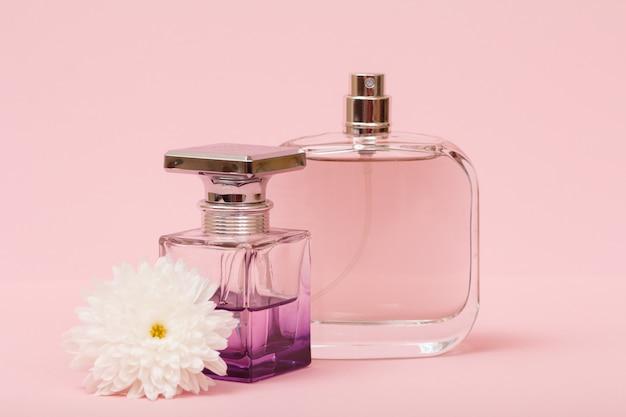 Bottiglie con profumi femminili e bocciolo di fiore in uno sfondo rosa. prodotti da donna.