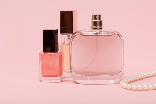 Bottiglie con profumi da donna, smalto per unghie e perline su uno spago su uno sfondo rosa. cosmetici e accessori donna.