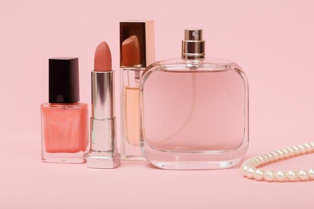 Bottiglie con profumi da donna, smalto per unghie, rossetto e perline su una corda su uno sfondo rosa. cosmetici e accessori donna.