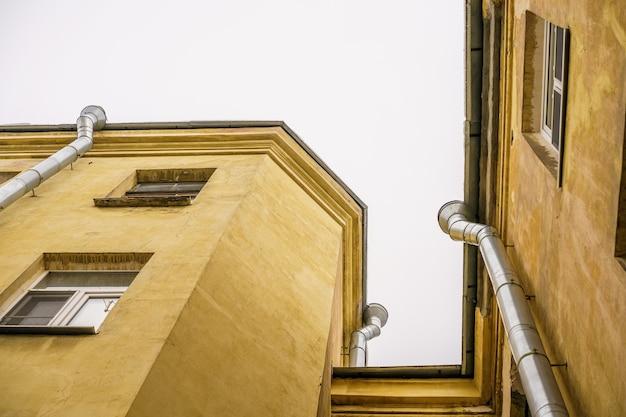 Vista dal basso verso l'alto del cielo e dei tetti dell'angolo del tetto della città vecchia e del pluviale sullo sfondo del cielo grigio