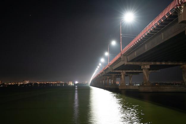 Vista dal basso di un bellissimo ponte lungo e luminoso con luci fredde e auto veloci sul grande e bellissimo fiume dnieper a dnepropetrovsk nella bellissima ucraina
