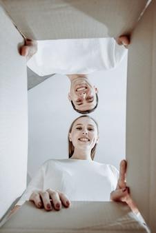 Vista dal basso di una bella giovane coppia che esamina la macchina fotografica e sorride mentre imballano o disimballano scatole in movimento