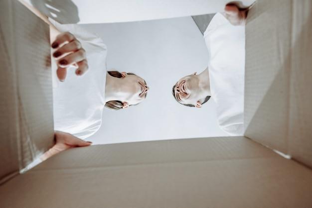 Vista dal basso di una bella giovane coppia che si guarda e sorride attraverso una scatola di cartone