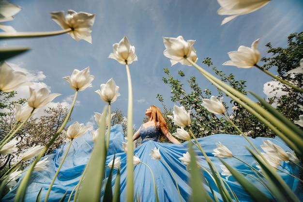 Vista dal basso bella giovane ragazza caucasica snella si trova vicino a tulipani in fiore bianchi in un elegante abito blu ondeggiante in una soleggiata giornata primaverile concetto di romanticismo e bellezza