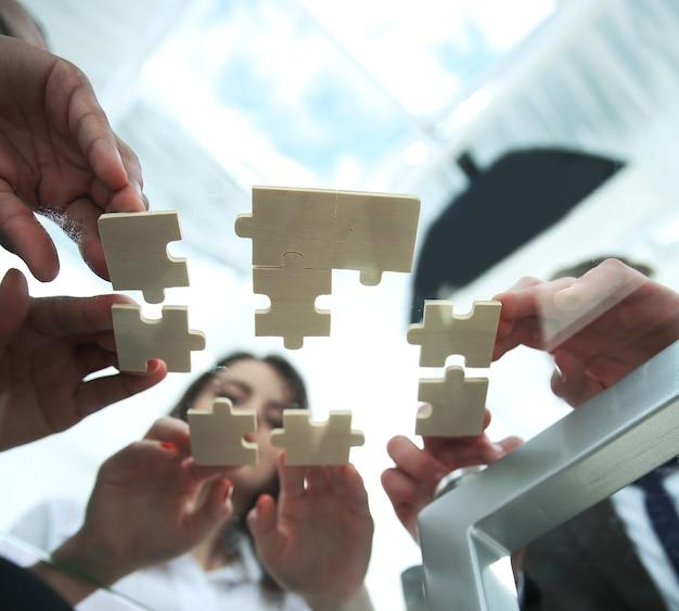 Vista dal basso business team pieghevole pezzi di puzzle concept soluzioni aziendali