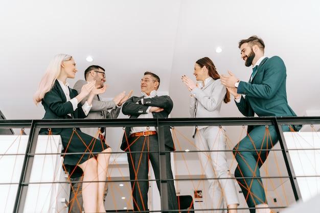 Vista dal basso dei colleghi in abbigliamento formale che applaudono con le mani al loro ceo per il successo degli affari. spingiti, perché nessun altro deve farlo per te.