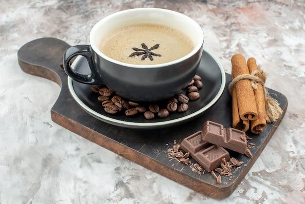 Vista dal basso tazza di caffè aromatizzata con cioccolato all'anice bastoncini di cannella su tavola di legno chicchi di caffè tostati nel piattino sul tavolo