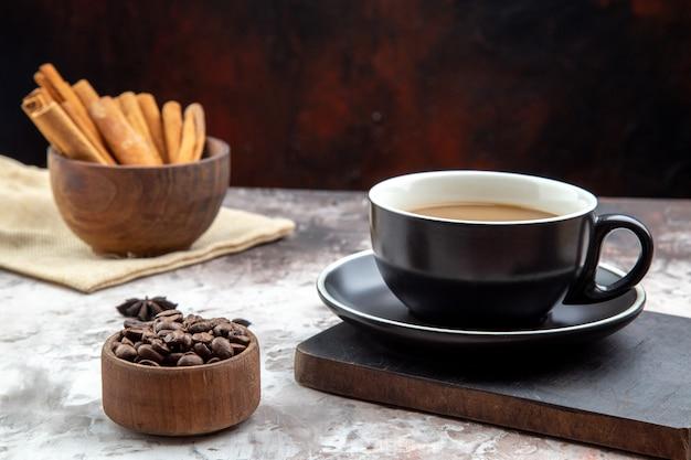 Vista dal basso tazza di caffè su tavola di legno ciotole con bastoncini di cannella e chicchi di caffè sul tavolo