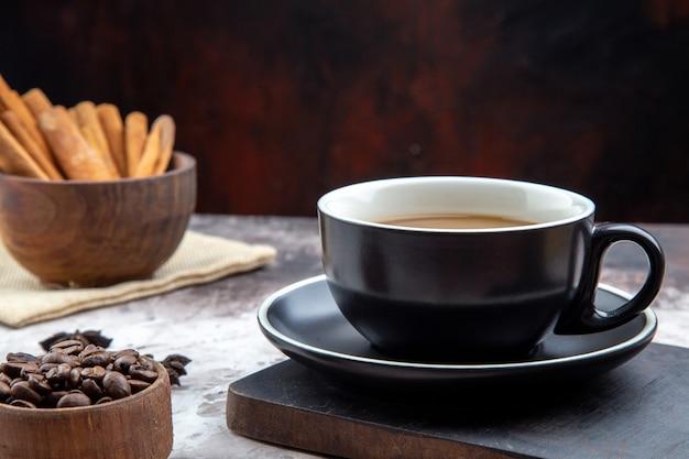 Vista dal basso tazza di caffè su ciotole di legno con bastoncini di cannella e chicchi di caffè tostati sul tavolo