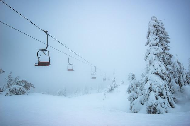 Vista dal basso ascensori turistici vuoti pendono sopra le colline