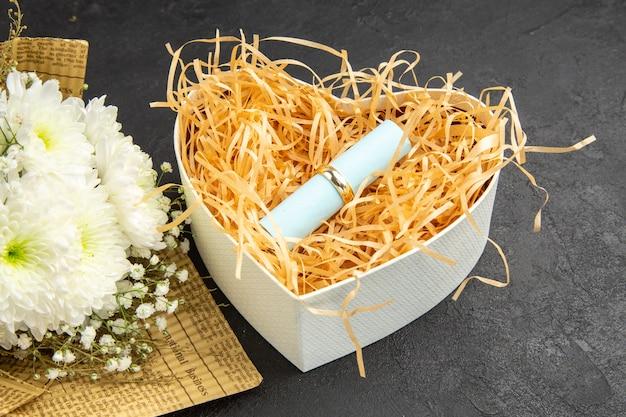 Vista dal basso anello di fidanzamento scorrere carta dei desideri in una scatola a forma di cuore bouquet di fiori su sfondo scuro