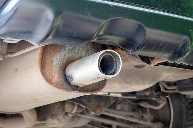 Vista dal basso del tubo di scarico dell'auto, parti e infissi arrugginiti e polverosi