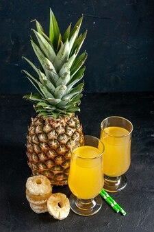 Vista dal basso ananas fresco fette di ananas secco pipette succo di ananas in bicchieri su sfondo scuro