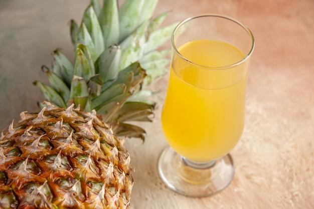 Vista dal basso succo di ananas fresco in vetro su fondo beige