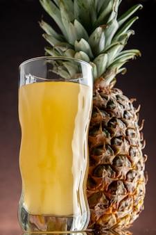 Vista dal basso succo di ananas fresco ananas su sfondo scuro