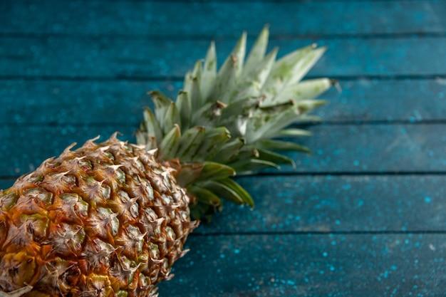Vista dal basso ananas fresco sdraiato su sfondo di legno blu