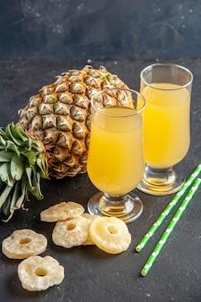 Vista dal basso ananas fresco che stabilisce fette di ananas secco succo di ananas in bicchieri pipette su sfondo scuro