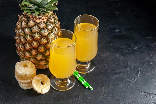 Vista dal basso pipette di ananas fresco fette di ananas secco succo di ananas in bicchieri su sfondo scuro