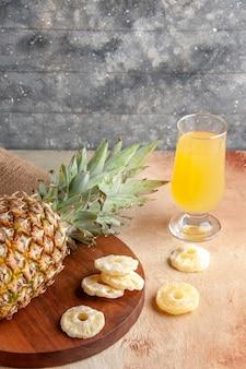 Vista dal basso ananas fresco su tavola di legno succo di vetro fette di ananas secche su fondo beige