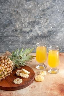 Vista dal basso ananas fresco su tavola di legno bicchieri di succo fette di ananas secche su sfondo beige
