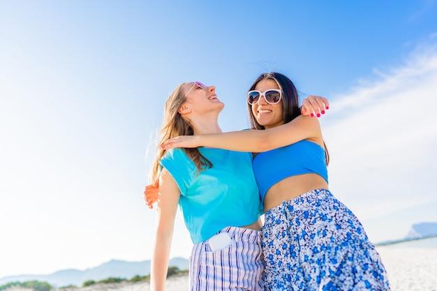Vista dal basso delle coppie di ragazze che abbracciano godendosi la vita durante le vacanze in mare ocean tropical resort