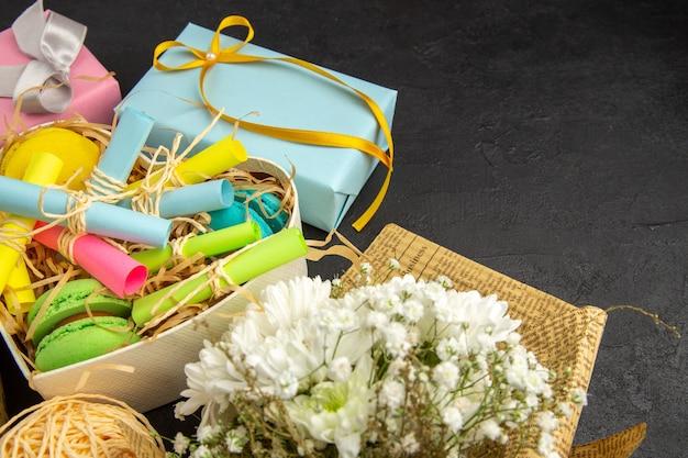 Vista dal basso scatola a forma di cuore con foglietti adesivi arrotolati e macarons regali blu e rosa bouquet di fiori su sfondo scuro