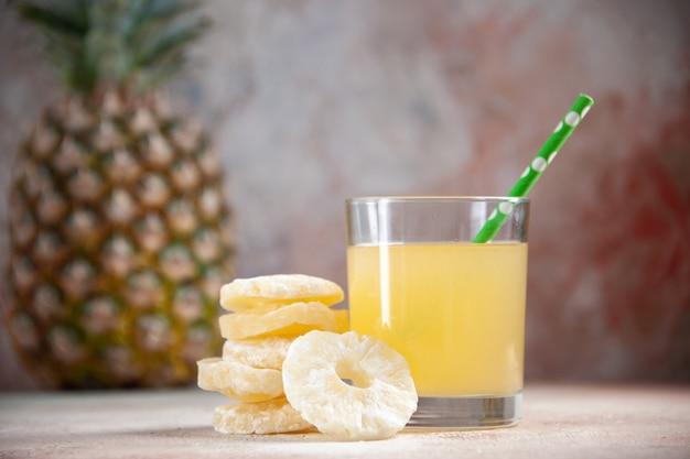 Vista dal basso succo pipetta in vetro ananas secco anelli ananas isolato su sfondo beige