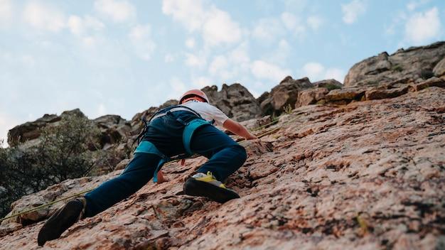 Vista dal basso di un bambino con i capelli castani che scala una montagna