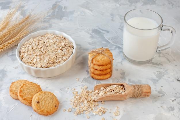 Vista dal basso bicchiere di latte biscotti avena ciotola spighe di grano su sfondo grigio