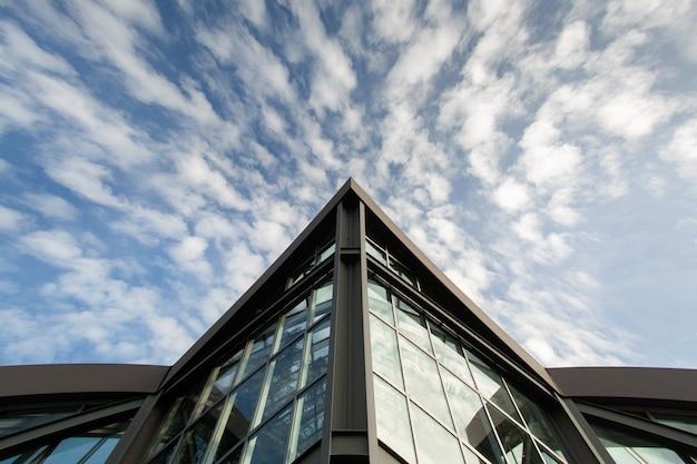 Vista dal basso di un edificio moderno a francoforte. l'angolo acuto di costruzione sullo sfondo del cielo con nuvole bianche. copia spazio