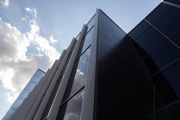 Vista dal basso di un edificio nuovo e moderno con pareti di vetro che riflettono il cielo
