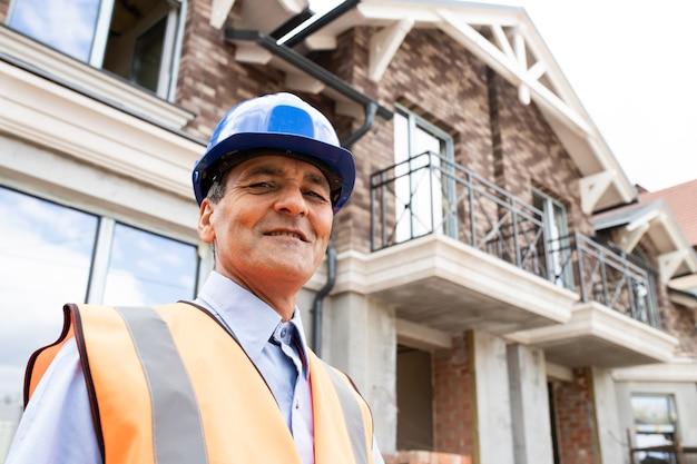 Vista dal basso del ritratto di gioioso architetto uomo indiano americano al cantiere guardando l'operaio edile della macchina fotografica che indossa elmetto protettivo blu e ovest che sorride alla macchina fotografica